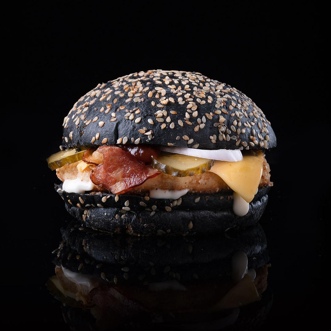 бургер с куриной котлетой, черная булка на черном фоне. фуд-фото